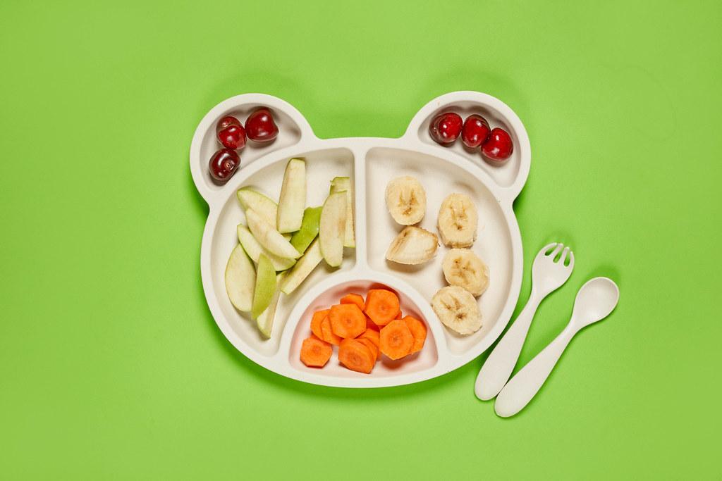 Fresh cherries, apple, banana and carrot slices on bear-shaped bamboo plate