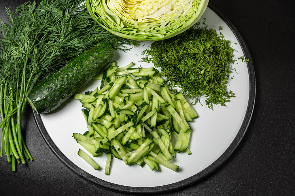 Fresh chopped cabbage, cucumber and dill for cooking salad, dark background