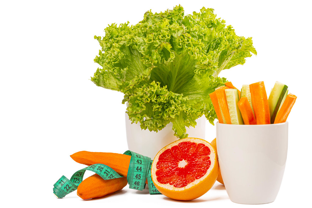 Fresh diet vegetables and half grapefruit on white background with measuring tape