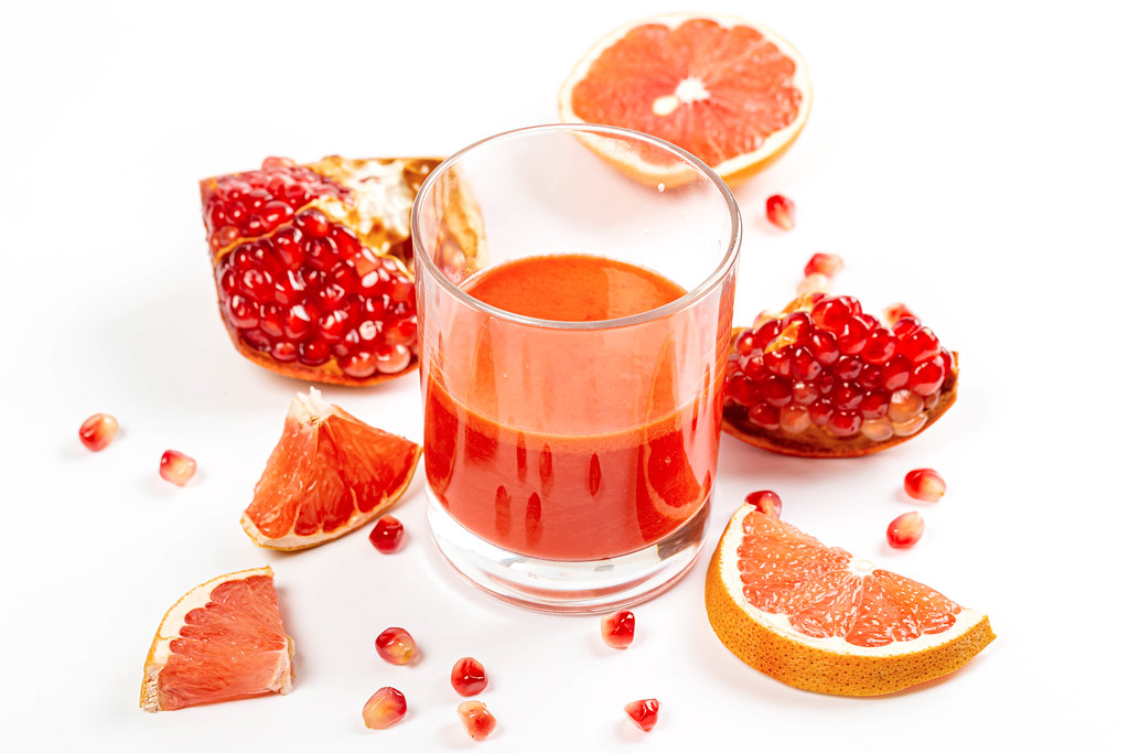 Fresh fruit grapefruit and pomegranate with a glass of juice on a white background