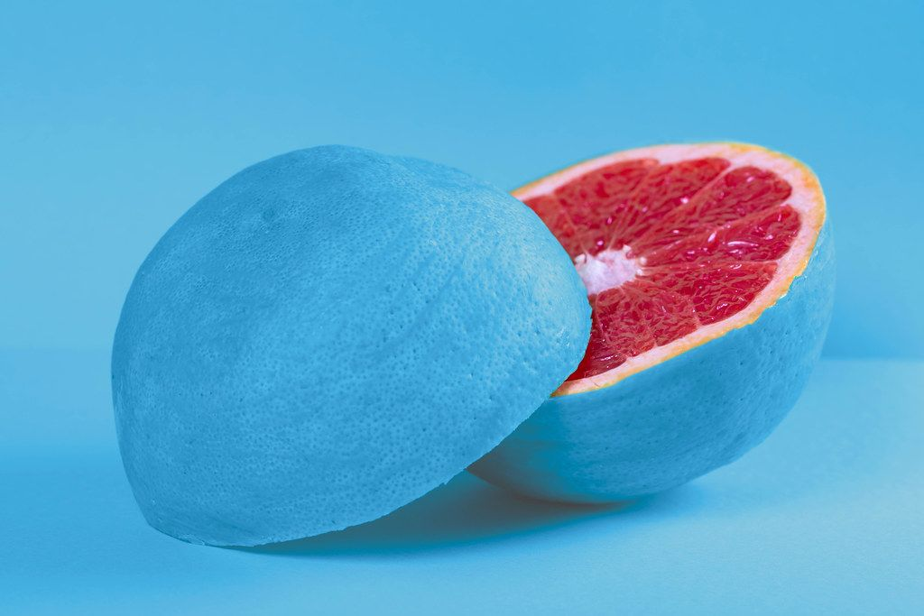 Fresh grapefruit halves with blue peel on blue background