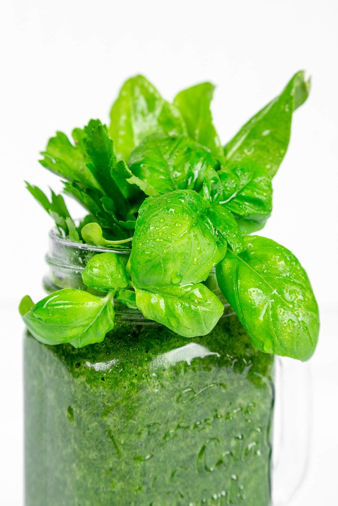 Fresh green smoothie with basil leaves in a glass jar, close-up
