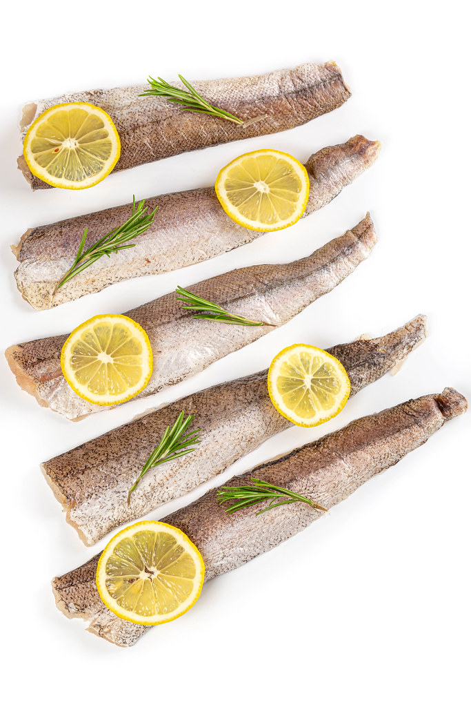 Fresh hake fillets ready to cook with lemon and rosemary
