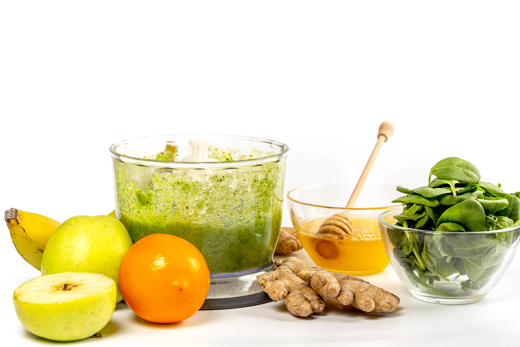 Fresh ingredients - lemon, apple, banana, honey, ginger and spinach on white with ready-made smoothie in blendew