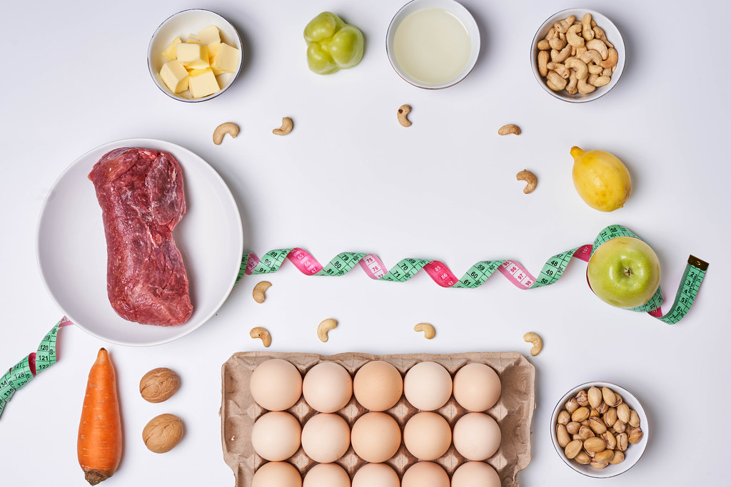 Fresh keto food and measuring tape on white background. Top view