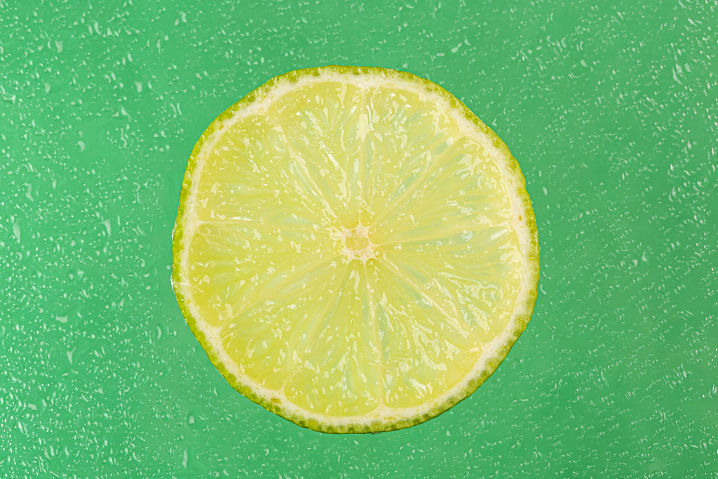 Fresh lime round slice on wet green background