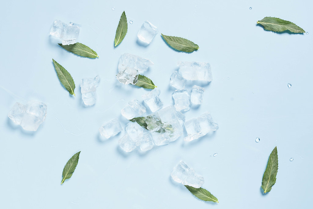 Fresh mint leaves and ice cubes on bright blue background