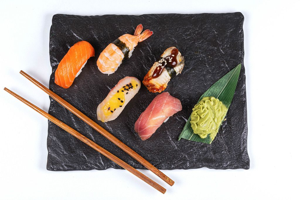 Fresh nigiri on a black stone tray with hot wasabi sauce, top view