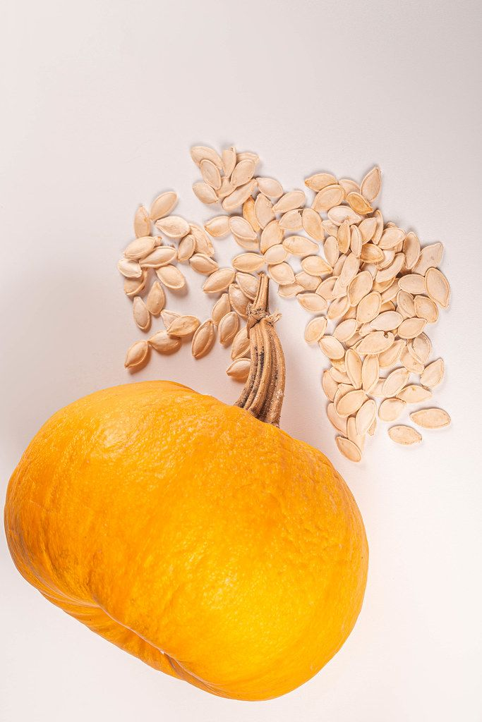 Fresh orange pumpkin and seeds on white background