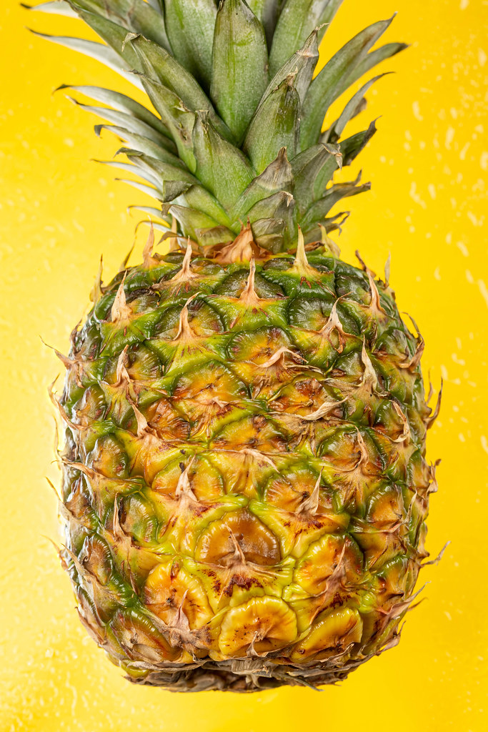 Fresh pineapple on wet yellow background