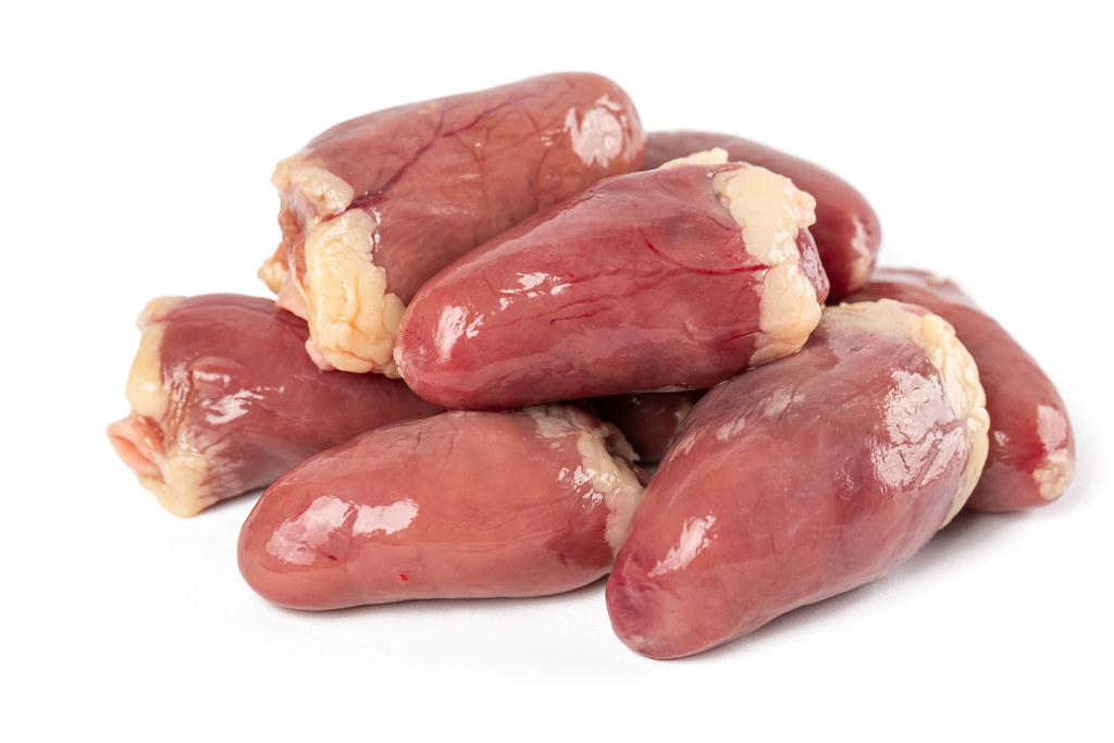 Fresh raw chicken hearts on white background