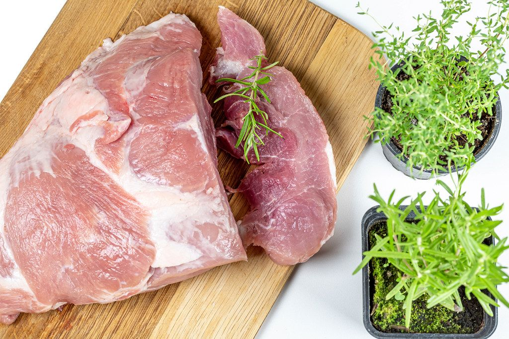 Fresh raw meat pork with rosemary and thyme