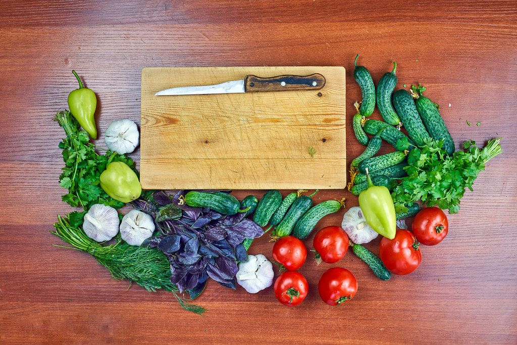 Fresh raw vegetables placed around the wooden cutting board