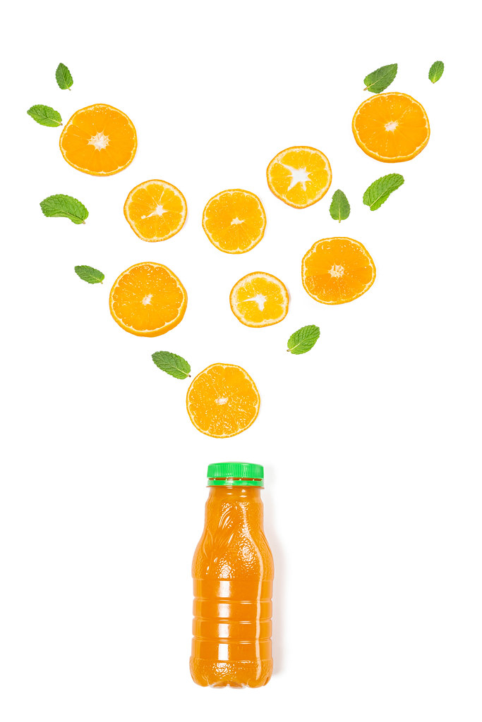 Fresh ripe orange slices and mint leaves on a white background with a bottle of juice