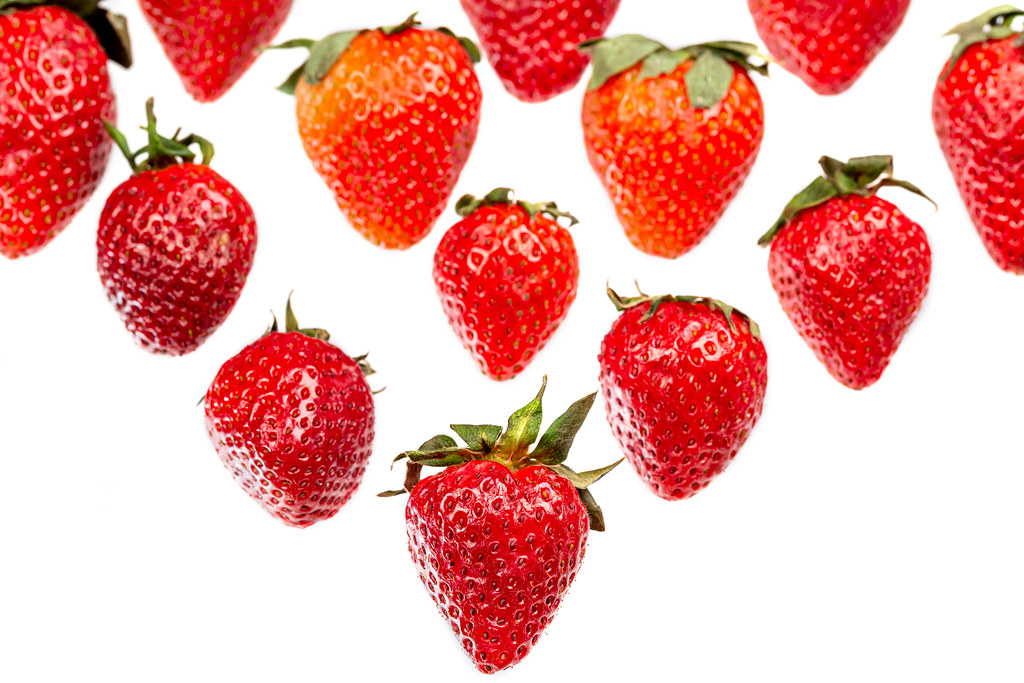 Fresh ripe strawberries with green leaves on white