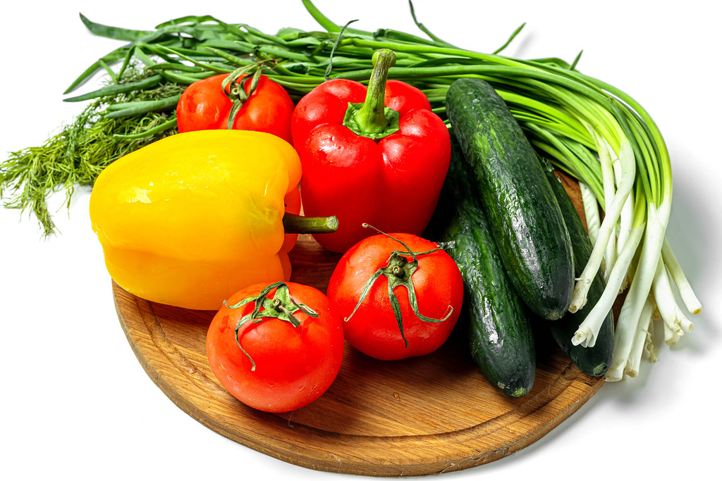 Fresh ripe vegetables and herbs on a wooden kitchen board