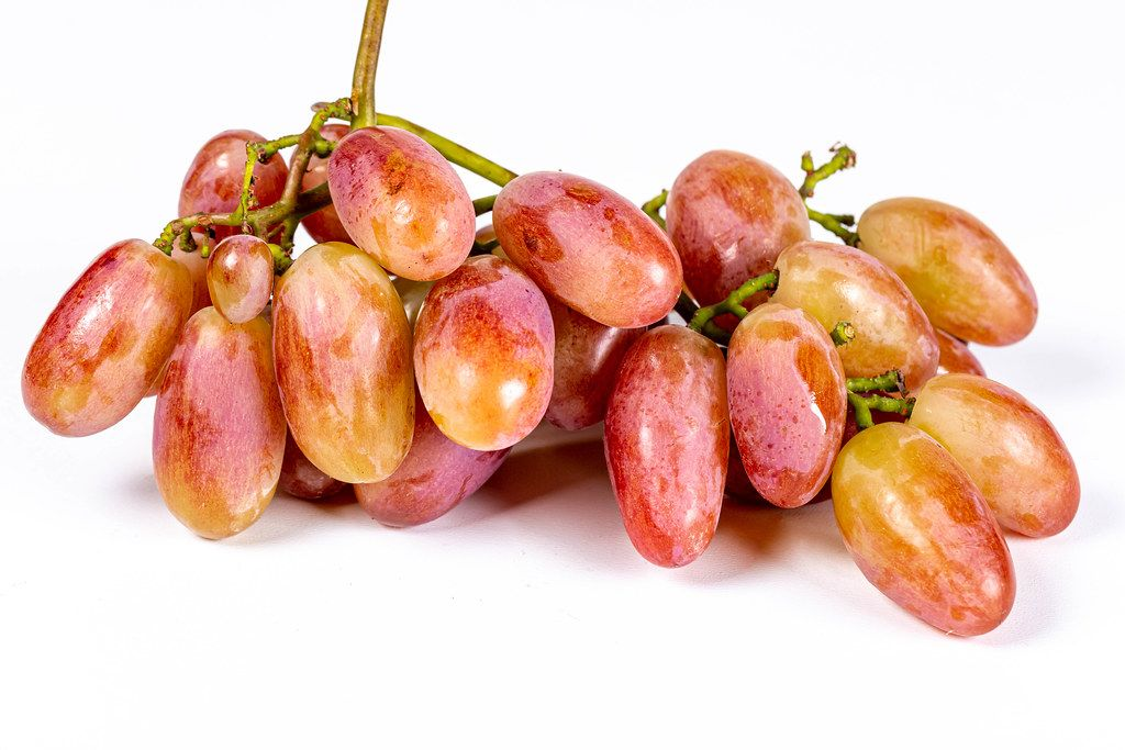Fresh ripe yellow-pink grapes on white