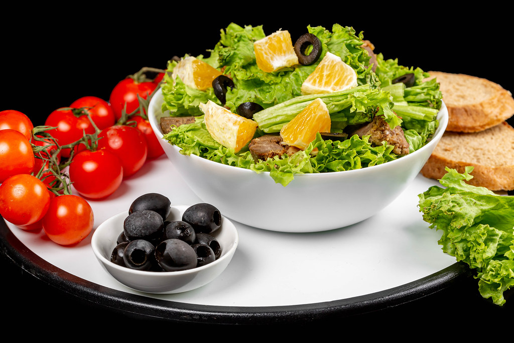 Fresh salad with lettuce, black olives, orange slices and liver, healthy food background