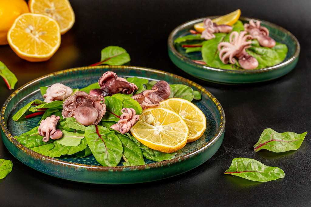Fresh salad with pickled octopus, beet leaves and lemon, dark background
