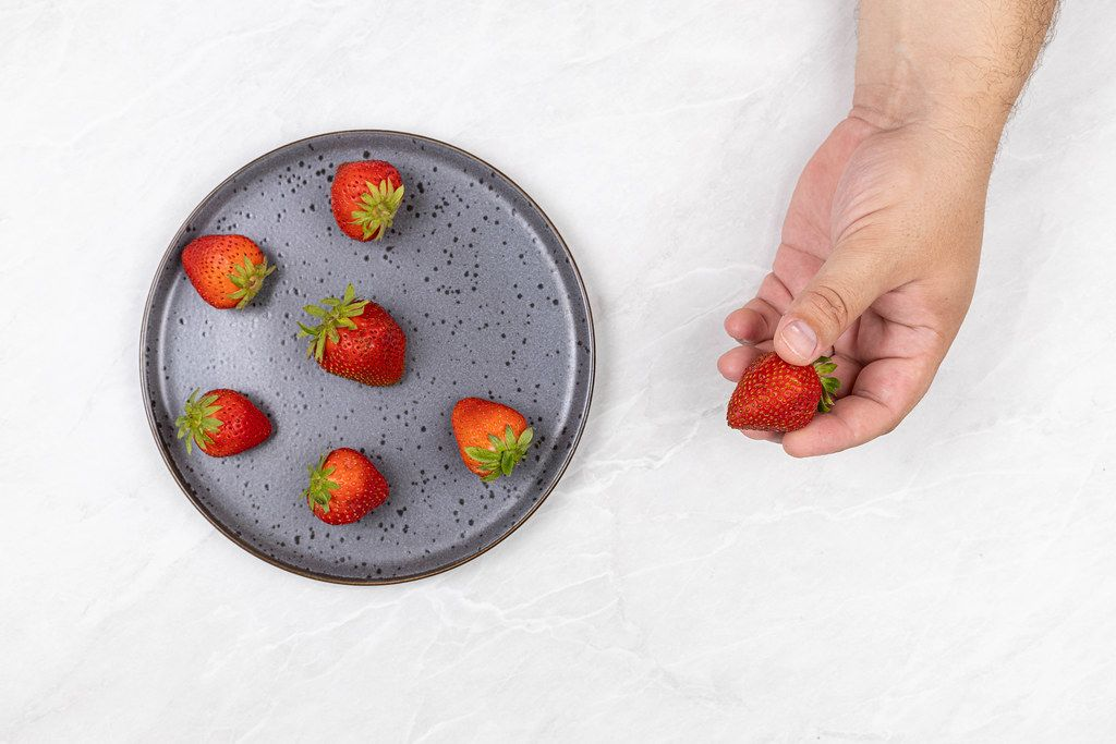 Fresh Strawberries served on the plate with strawberry in the hand
