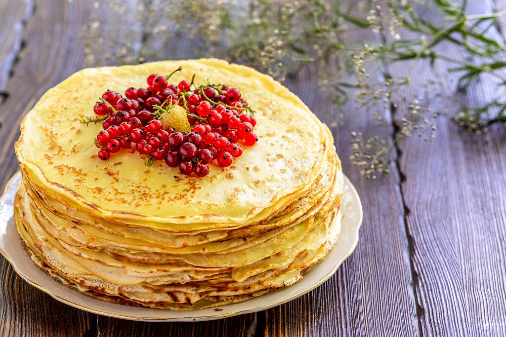 Fresh thin pancakes with red currant berries on a brown wooden background with belima flowers