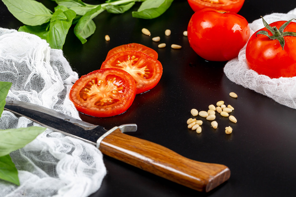 Fresh tomatoes with pine nuts, basil, knife and gauze on black background