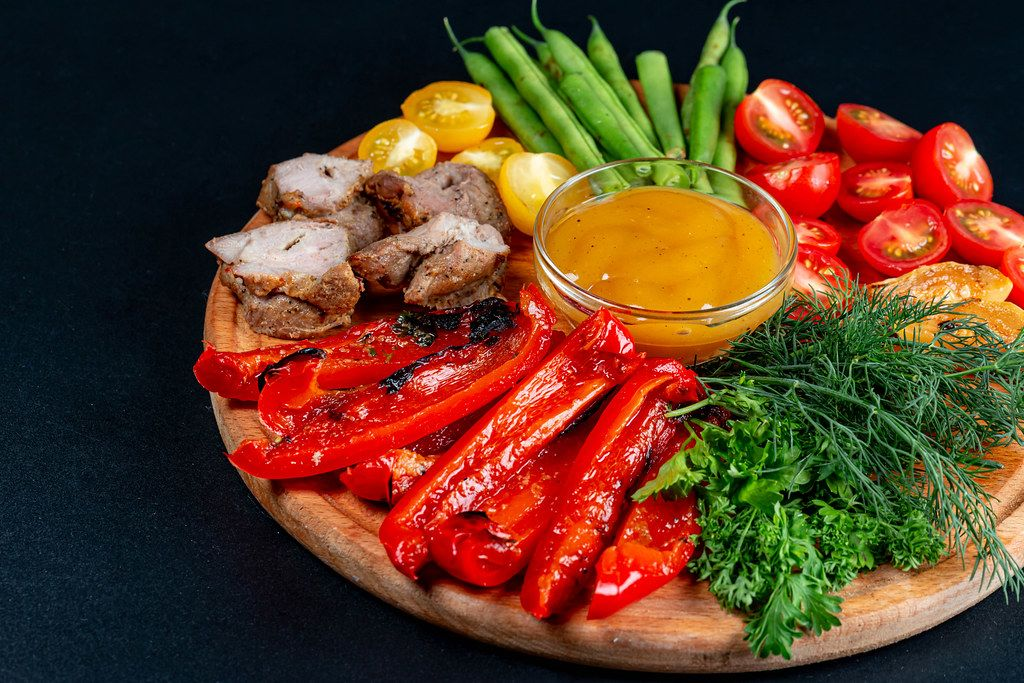 Fresh vegetables and greens with grilled vegetables and meat on a black background
