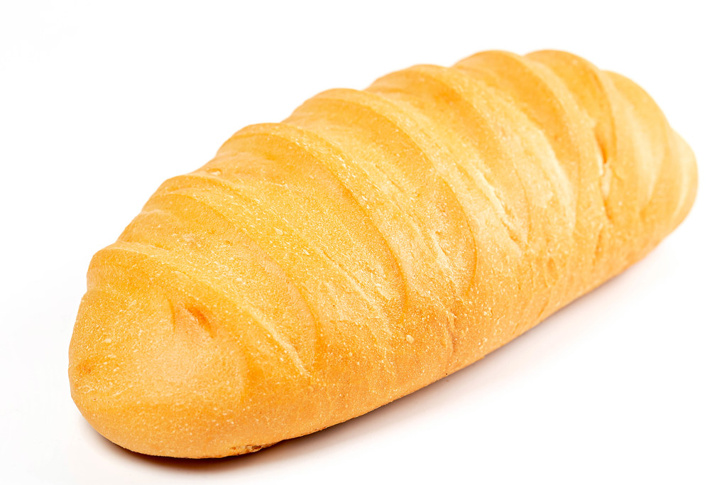 Fresh wheat loaf on white, close-up