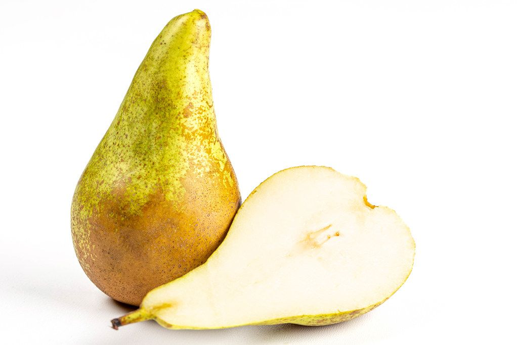 Fresh whole and half pears on a white background