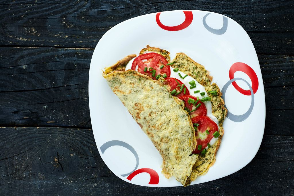 Freshly cooked omelet with herbs, sour cream and tomatoes