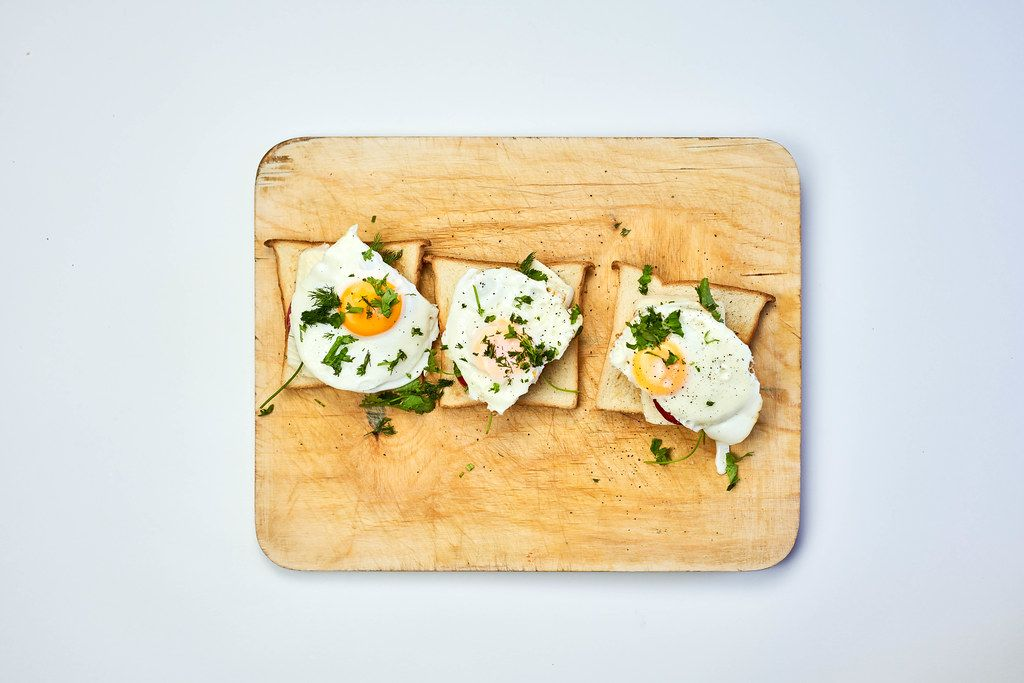 Freshly fried eggs with herbs on cutting board