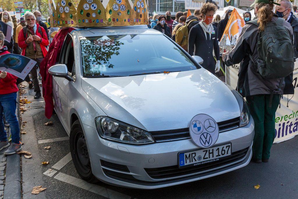 Fridays for Future Demonstranten mit Maske und ein Auto mit Krone und BMW, Mercedes und VW Logos