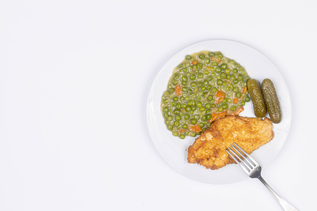 Fried Chicken breasts with cooked Green Peas with copy space