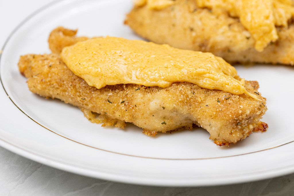 Fried Chicken White Meat in breadsrumbs with cheese sauce on the top