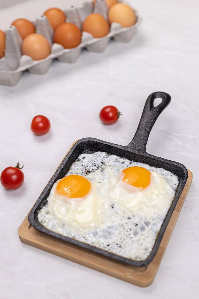 Fried Eggs in the frying pan with Cherry tomatoes with eggs in the box