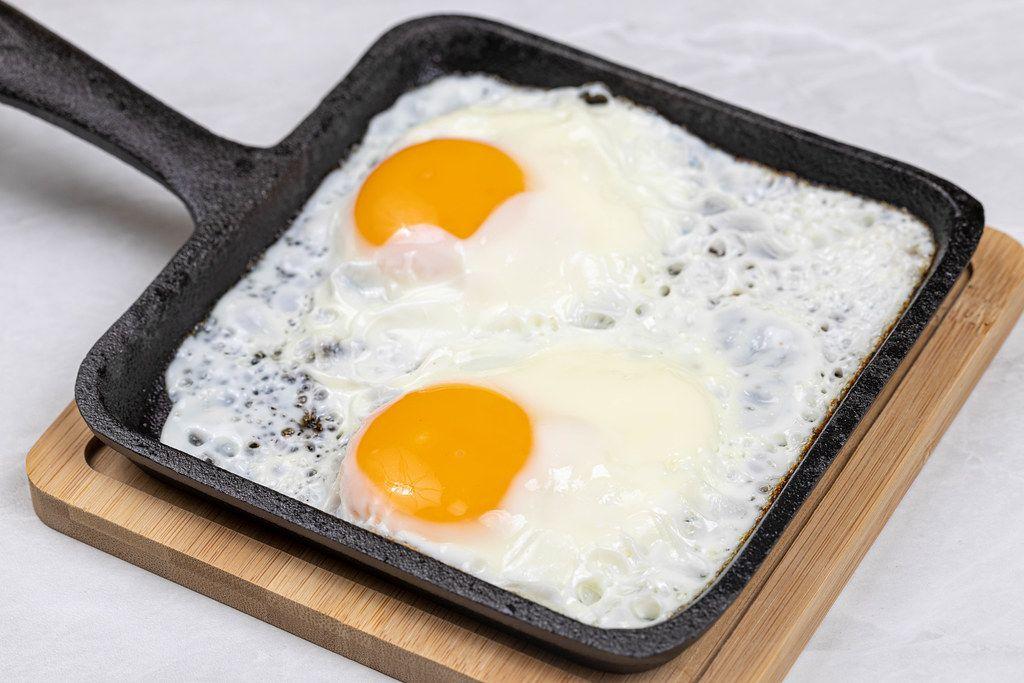 Fried Eggs in the hard black frying pan