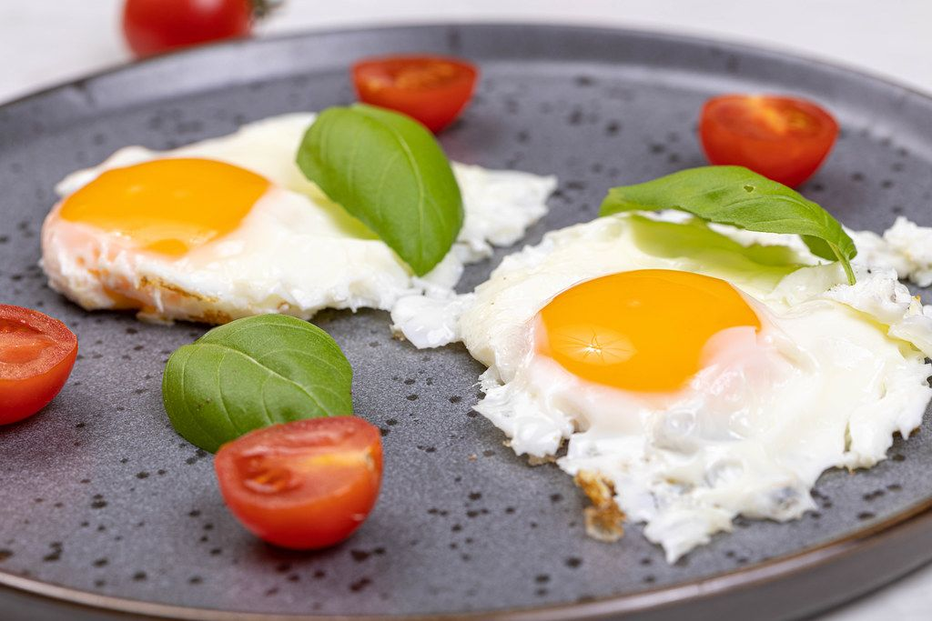 Fried Eggs served with Cherry tomatoes and Basil