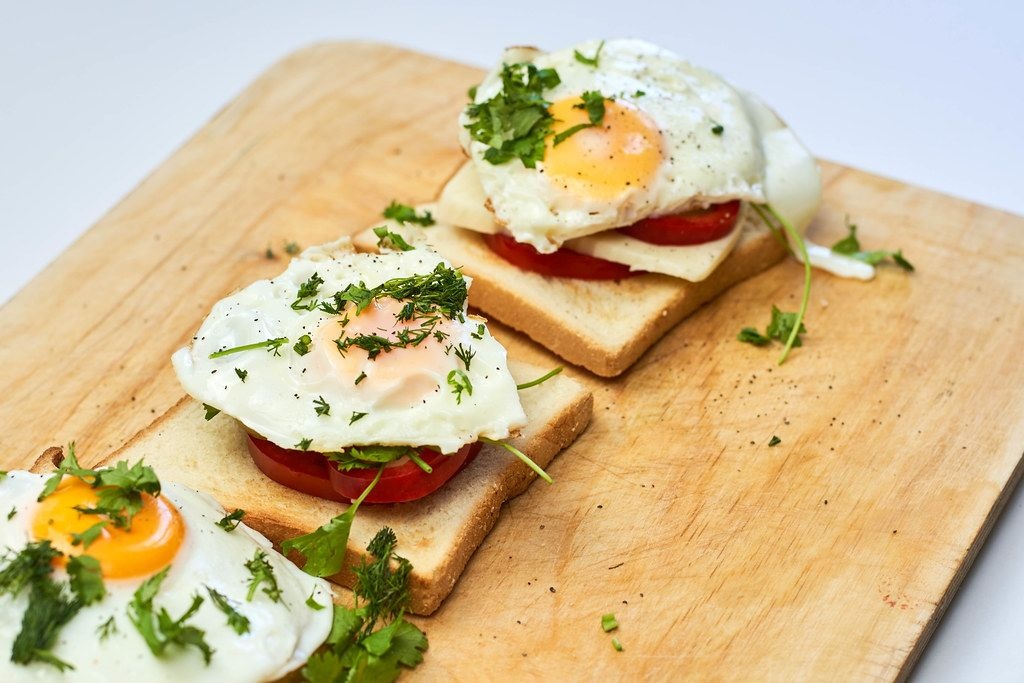 Fried eggs with toasted bread and parsley on wooden cutting board