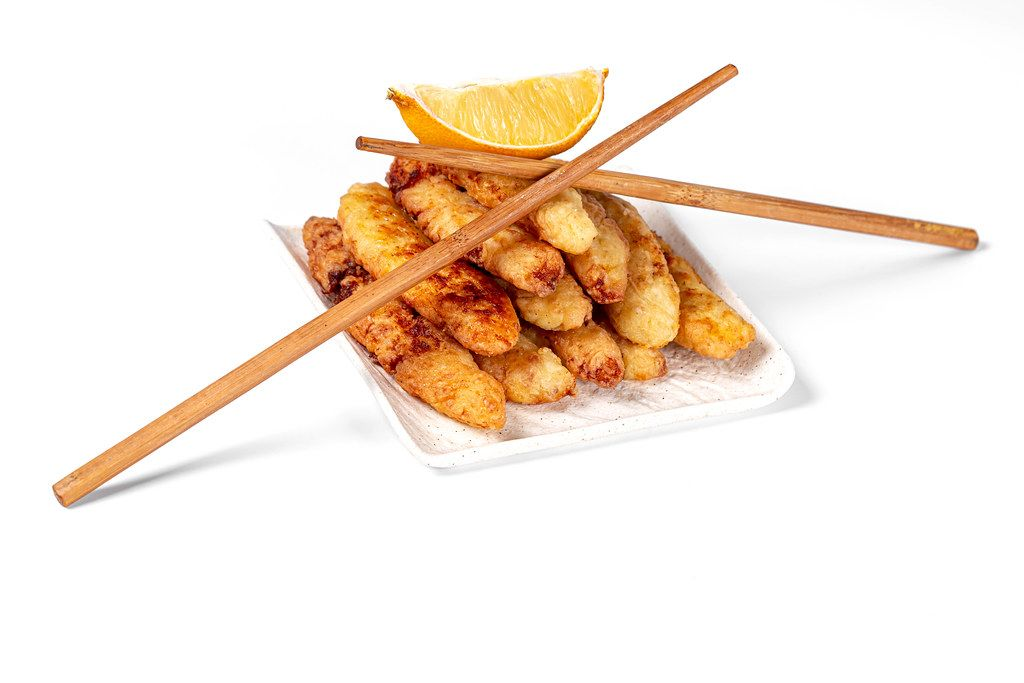 Fried fish sticks with a slice of lemon and chopsticks