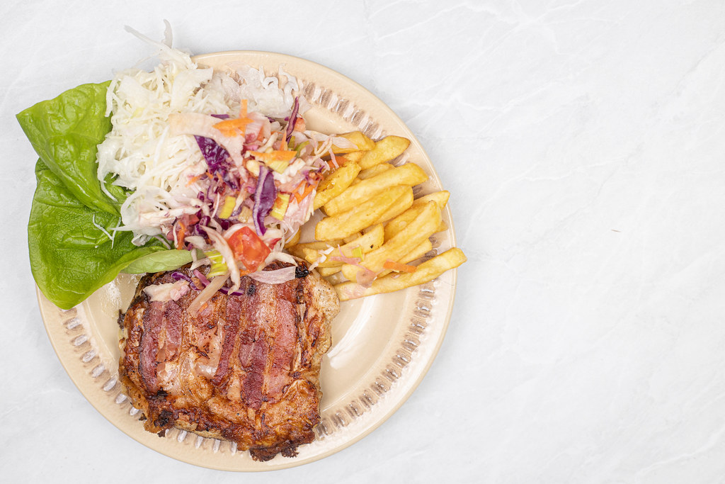 Fried Pork Meat in Bacon with cabbage salad and french fries