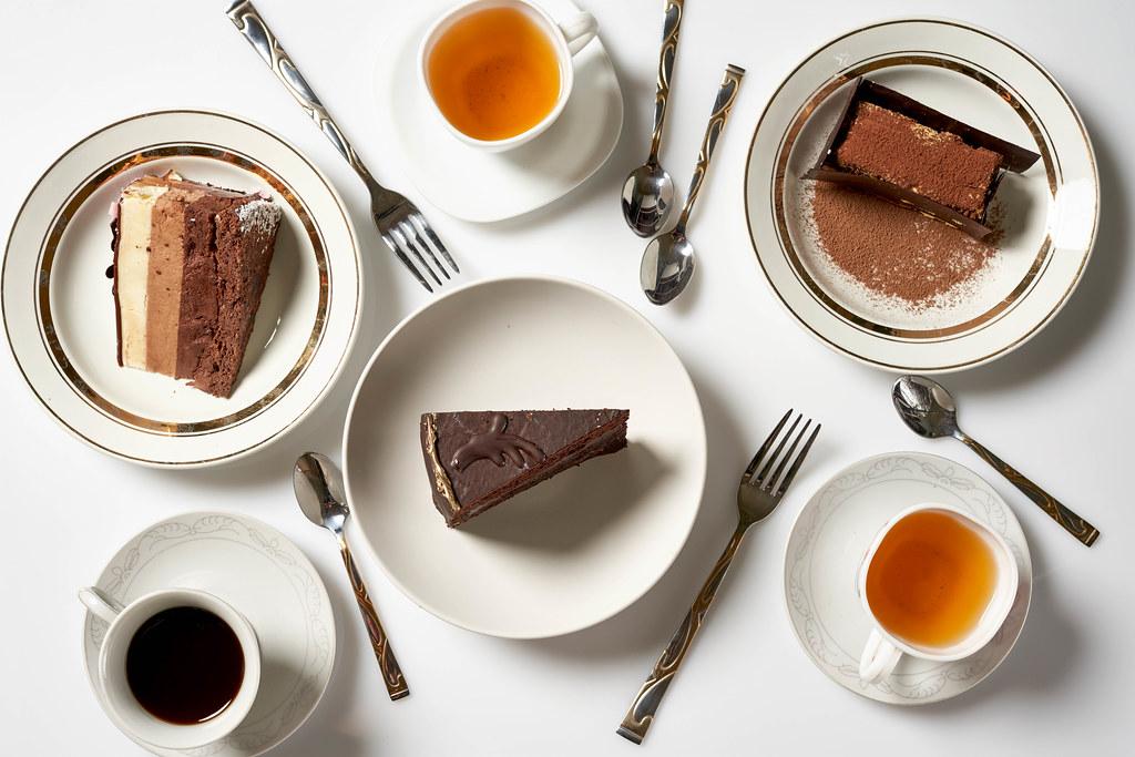 Frühstück für drei: Kaffee- und Teetassen, drei verschiedene Tortenstücke und Besteck