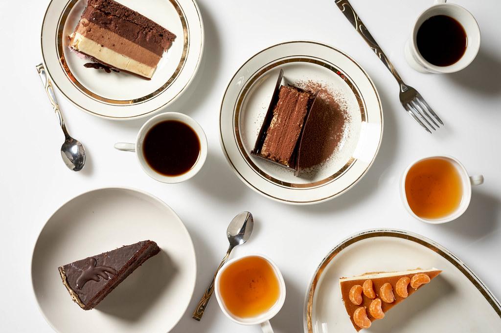 Frühstück für vier: Kaffee oder Tee mit Kuchen oder Torte. Aufnahme von oben vor weißem Hintergrund