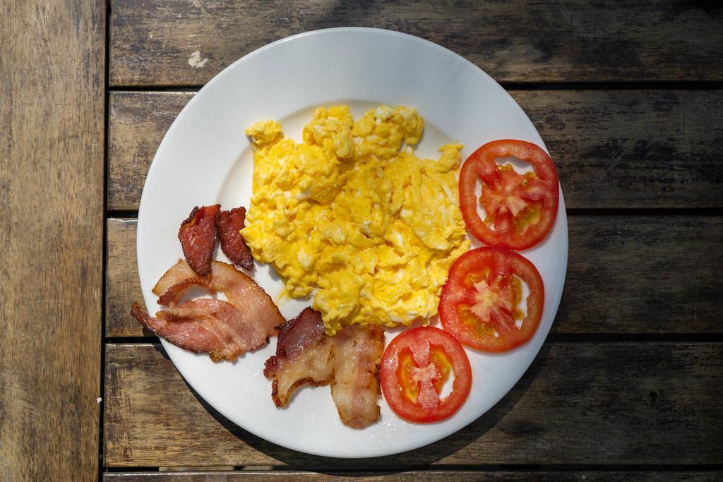 Frühstücksteller mit Rührei, gebratenen Speckstreifen und Tomatenscheiben von oben auf einem Holztisch fotografiert