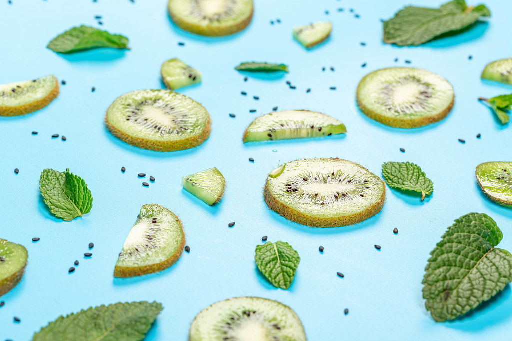 Fruit background with fresh kiwi slices, black sesame seeds and mint leaves on blue