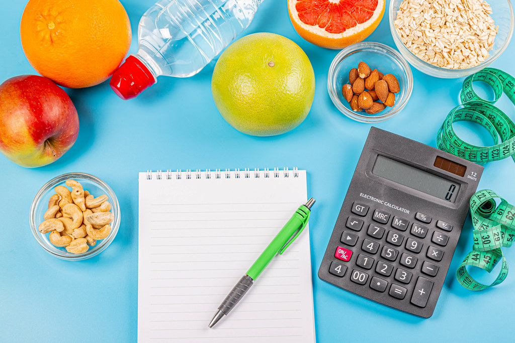 Fruits, oatmeal, nuts, calculator, bottle of water and measuring tape on blue background with notepad and pen