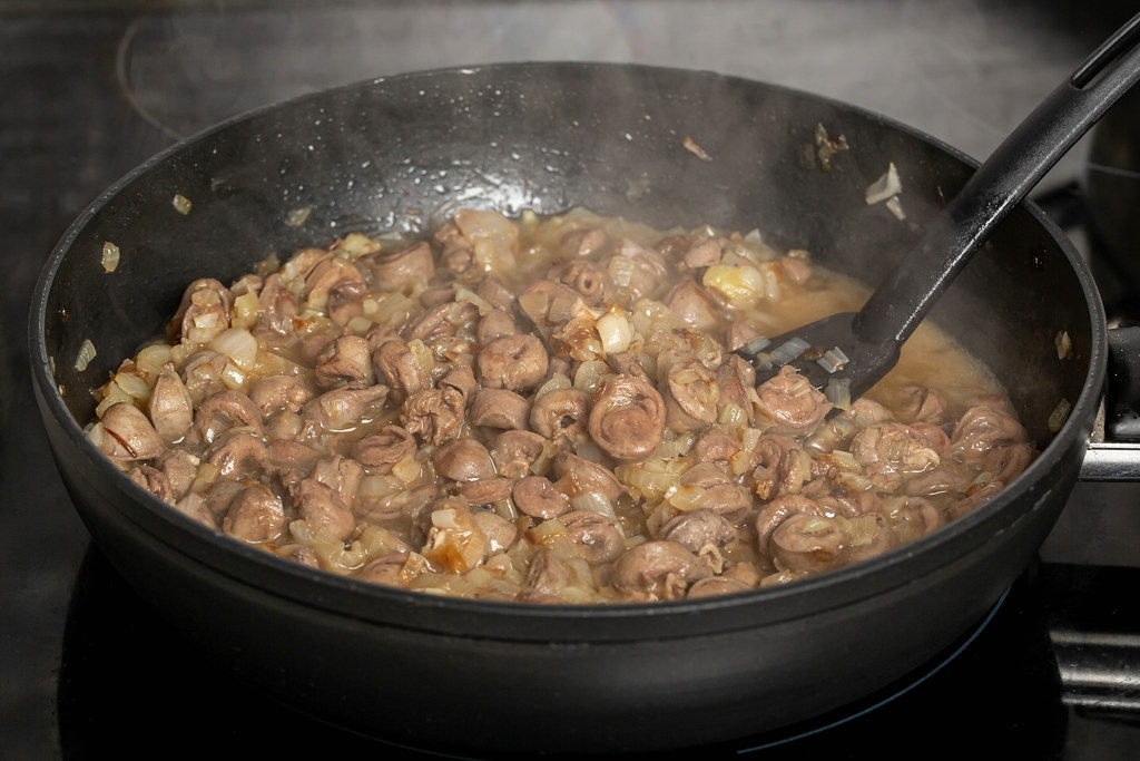 Frying pan with fried chicken hearts and onions, cooking process