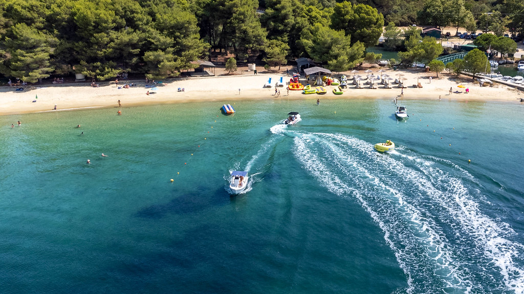 Fun at sea: motorboats and aquadonuts in front of the beach Chrysi Ammos on Skiathos, Greece