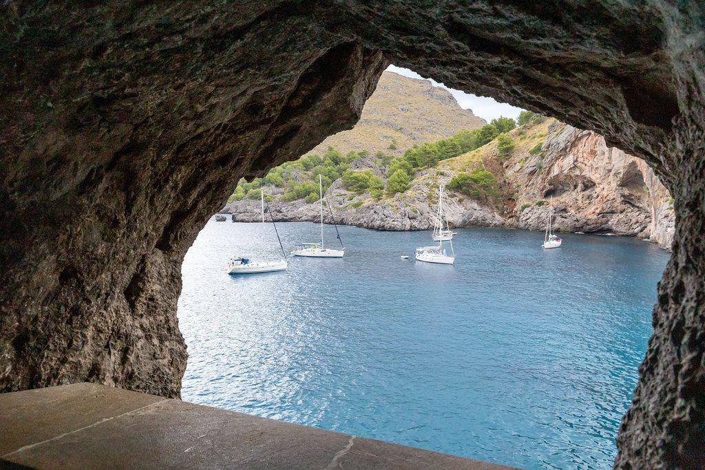Fünf Segelboote im blauen Wasser in einem Felsenfenster eingerahmt. Sa Calobra, Mallorca