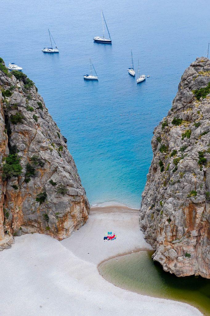 Fünf Segelboote und ein Motorboot vor dem Strand von Cala de sa Calobra auf Mallorca. Luftaufnahme