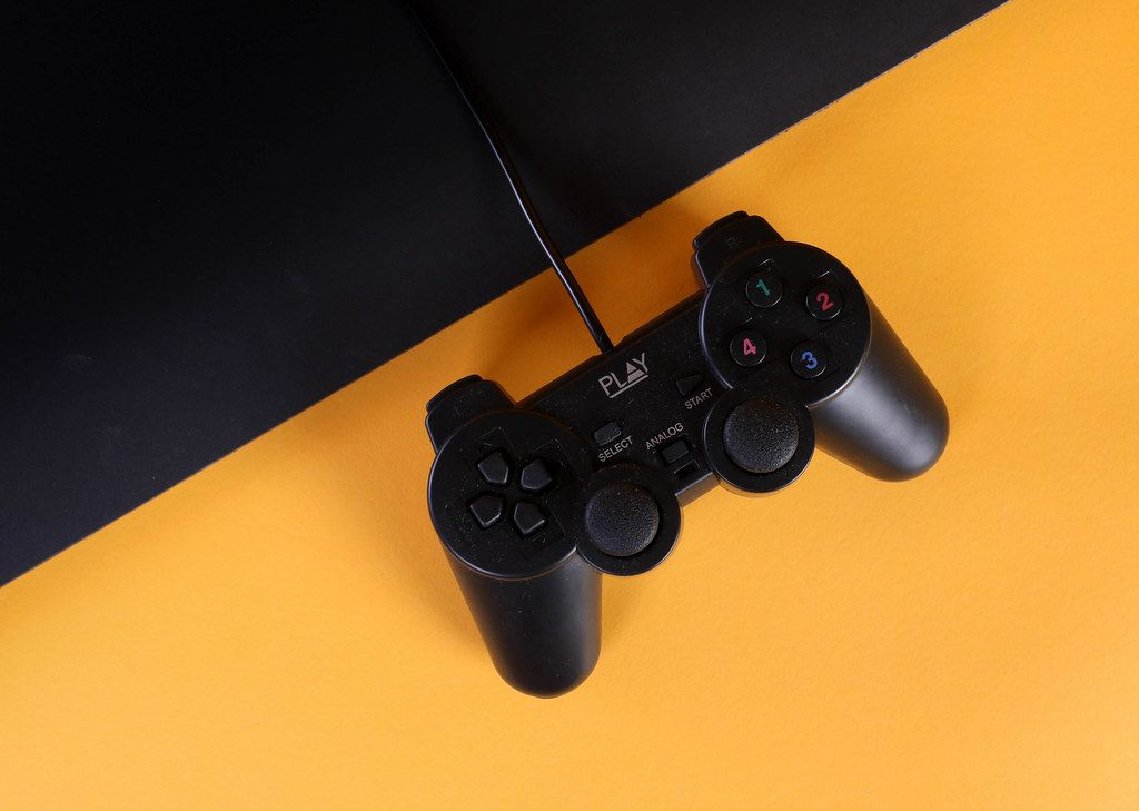 Gamepad with a cord on a orange and black background